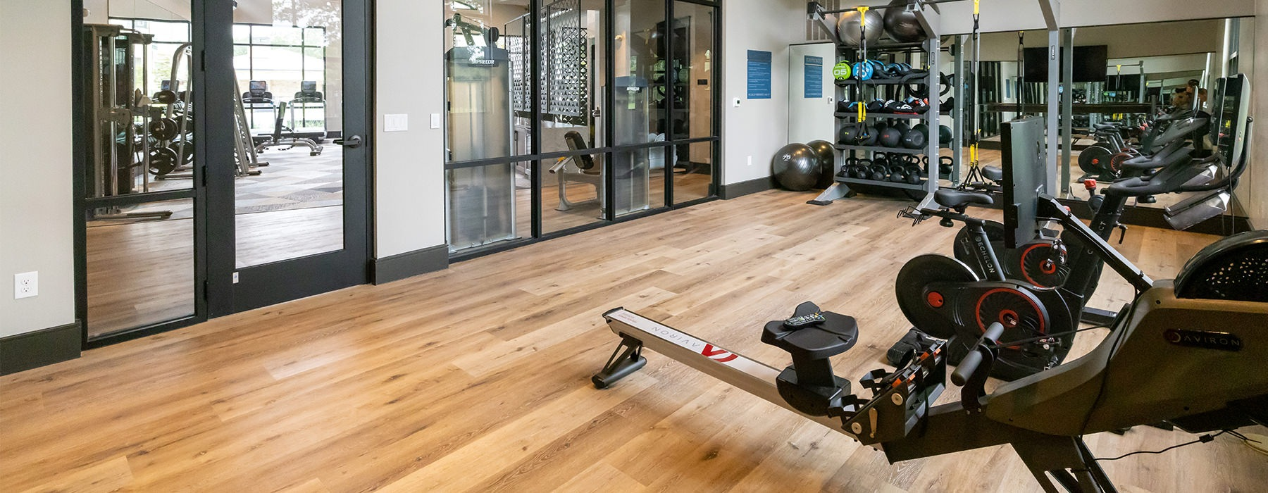 Spacious well lit gym with wood floors and weight machines