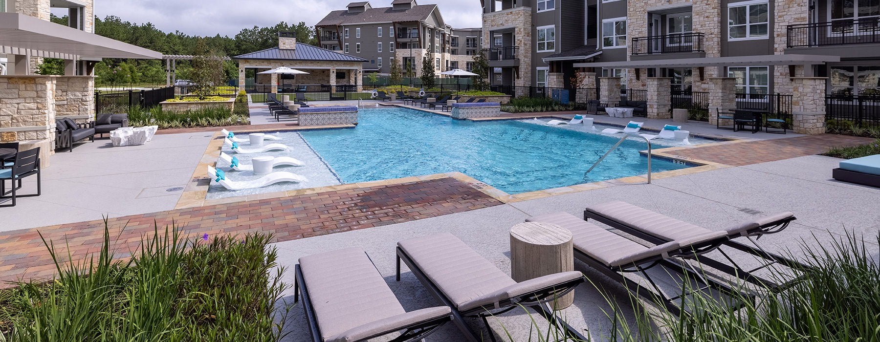 Large resort style sparkling blue pool with large sundeck